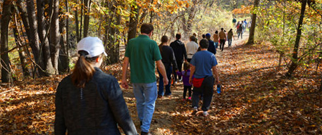naturalist leading a group for a hike in park during fall season