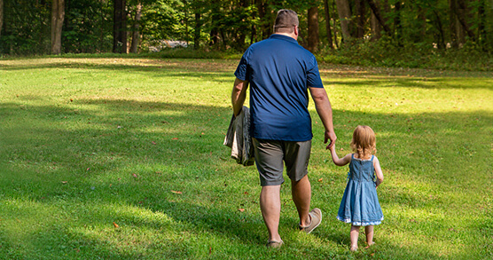 father and daughter walk through grass in park